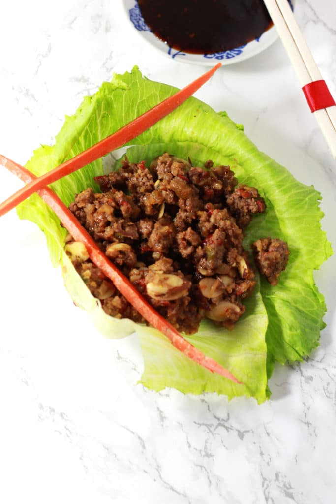 A close up of an Asian lettuce wrap with two long carrot sticks on a white table.