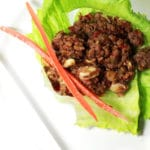 A close up of lettuce wrap with long carrot sticks on a white table.
