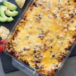 Mexican Style Casserole continuing beef, beans, tomatoes, and cheese, avocado, tomatoes, and tortilla chips on side.
