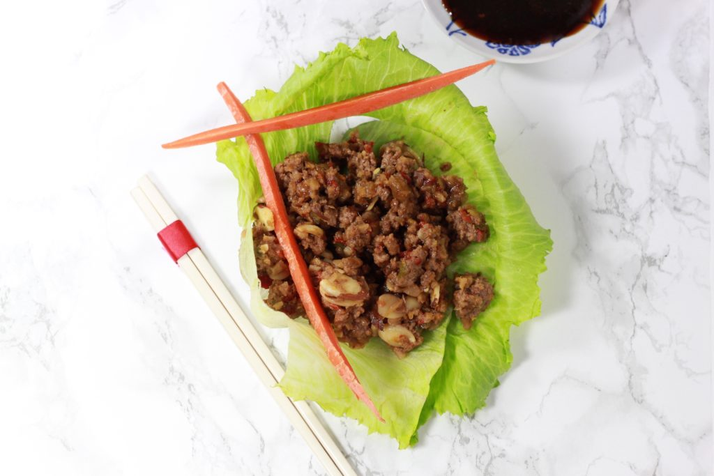 Lettuce wrap, small dish of soy sauce with long carrot sticks next to chopsticks on a white table.