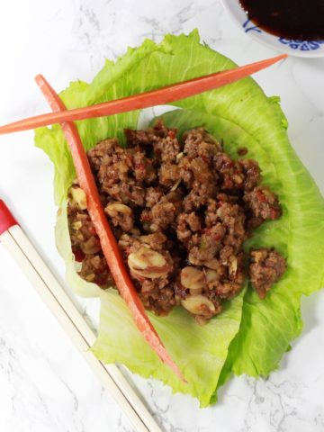 A close up of lettuce wrap with long carrot sticks next to chopsticks on a white table.