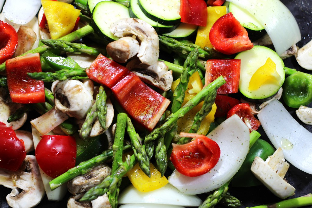 A sheet pan filled with oven roasted vegetables containing peppers, asparagus, mushrooms and zucchini.