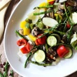 White platter containing oven roasted vegetable including asparagus, zucchini, squash, green peppers and onions.