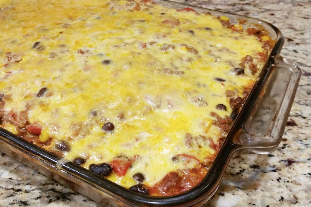 Clear Pyrex dish containing a beef, bean and cheese enchilada casserole.
