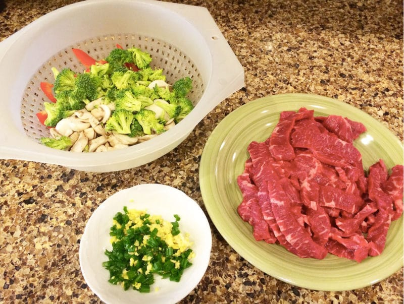 A large strainer with broccoli, mushrooms, and red pepper next to a plate of thinly sliced flack steak.