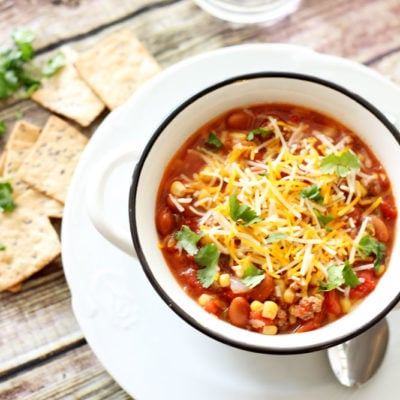 White bowl containing a southwest stew with tomatoes, beans and corn, topped with shredded cheese, crackers and cilantro on table.