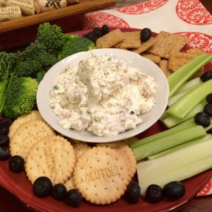 A close up of appetizer tray with crackers, broccoli, and celery