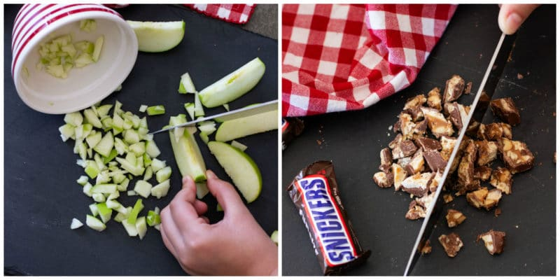 Person chopping granny smith apples and snickers bars on a black cutting board.