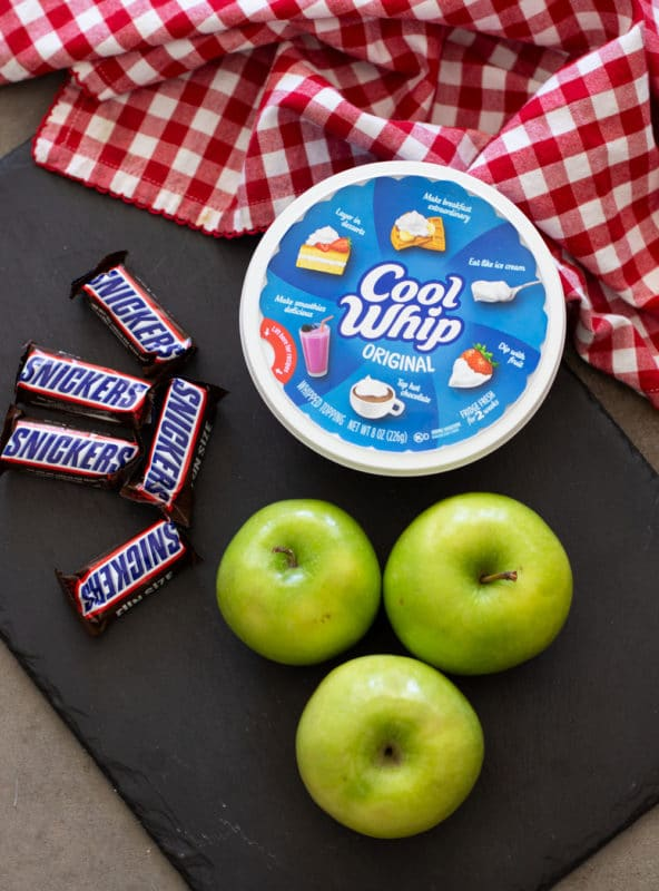 Cool whip, granny smith apples, and snickers bars on a black cutting board.