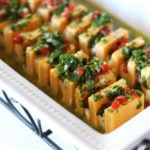 White glass dish containing orange and white marinated cheese topped with parsley, pimentos and garlic.