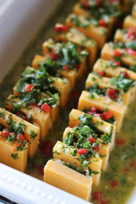 Appetizer of sharp cheddar cheese and cream cheese marinated and topped with parsley, pimentos, olive oil and garlic.