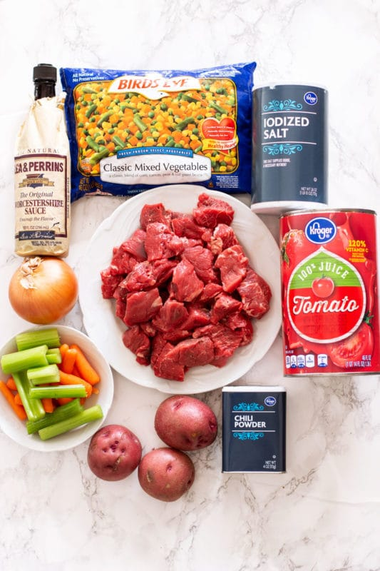 Ingredients for Vegetable Beef Soup on a table, beef stew meat, tomato juice, salt, mixed vegetable, Worcestershire sauce, onion, celery, carrots, potatoes, chili powder.