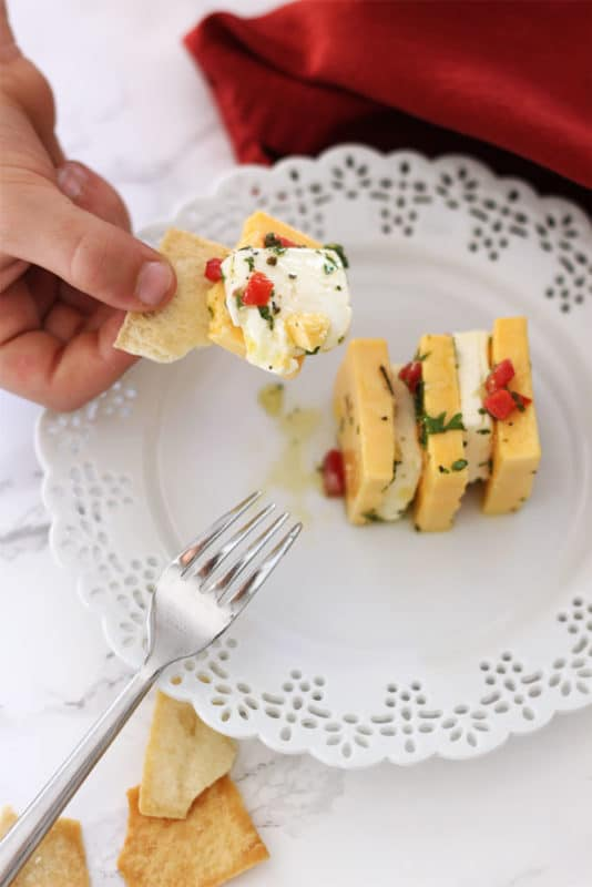 White lace plate with pita chips on the side, hand holding a pita chip covered with sharp cheddar and cream cheese, topped with pimentos, parsley, olive oil and garlic.