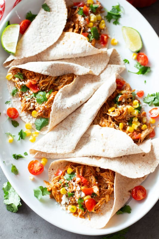 4 soft corn taco shells filled with shredded chicken, topped with cilantro, corn, and cheese.