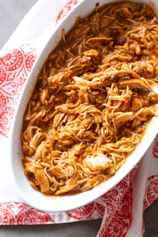 White bowl containing shredded chicken cooked in salsa.