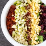 White bowl containing a salad with lettuce, bacon, pears, pecans, cheese, and dried cranberries.