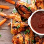 White plate containing 5 BBQ wings with BBQ sauce topped with fresh parsley sitting on a wooden table, carrots scattered.