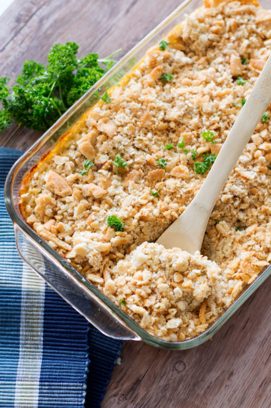 Chicken and Rice Casserole served in a glass casserole dish, white bowl of casserole on wooden table.