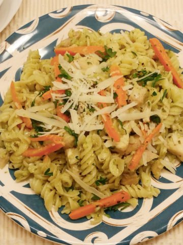 A blue decorative plate with rotini noodles with sliced carrots, basil pesto sauce, and sprinkled with parmesan cheese.