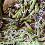 Baked green beans and mushrooms topped with Parmesan Cheese, wooden spoon in dish.