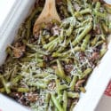 Roasted green bean with mushrooms topped with Parmesan cheese, serving spoon in dish.