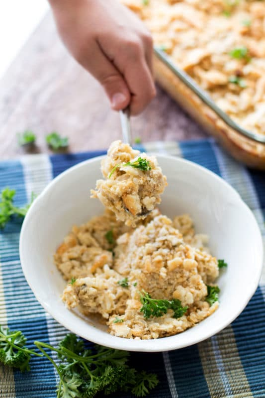 Hand holding a spoonful of Chicken and Rice Casserole over a white bowl filled with casserole.