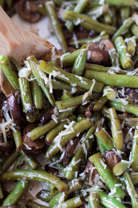 Close up of roasted green beans topped with Parmesan cheese.