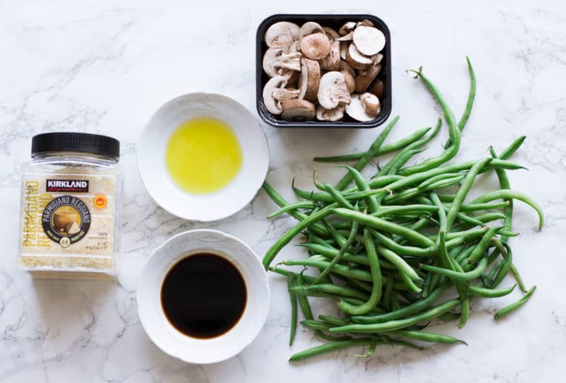 Fresh green beans, mushrooms, Parmesan cheese, olive oil and balsamic vinegar on marble table.