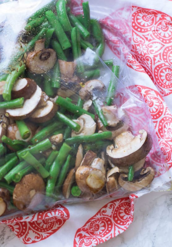 Ziplock bag marinating fresh green beans and mushrooms with olive oil and balsamic vinegar.
