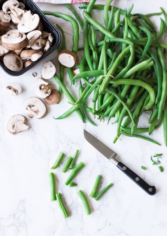 Chopped fresh green beans on counter, sliced mushrooms on table.