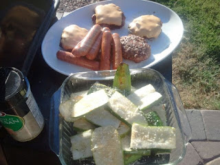 A dish of sliced grilled zucchinis on the side table of a grill with cheeseburger patties and hotdogs.