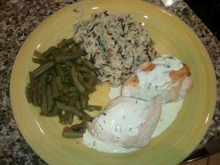 A close up of chicken breasts smothered in a mustard cream sauce with cut green beans and rice sides.