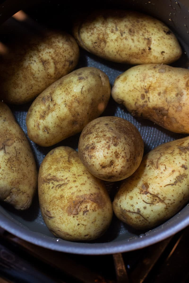 Pot with water containing potatoes ready to boil.