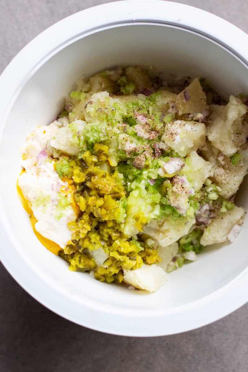 White bowl containing diced potatoes, celery, red onion, mustard, mayonnaise, and dill relish.