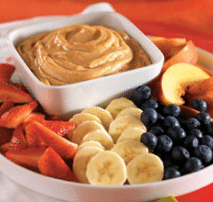 A white fruit serving tray with sliced bananas, strawberries, blueberries, and peaches with peanut butter and yogurt dipping sauce.