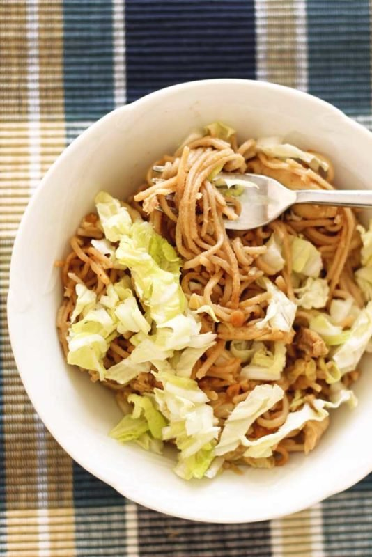 White bowl containing Thai Peanut Chicken Pasta, sitting on a blue placement map topped with cabbage, silver fork in noodles.