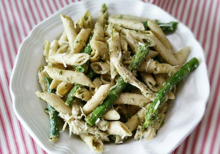 A white plate of penne rigate pasta with asparagus spears and parmigiano-reggiano cheese.