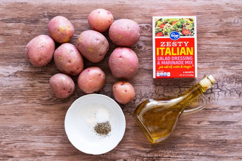 10 red potatoes, bottle of olive oil, zesty Italian marinade and spices on a wooden table.