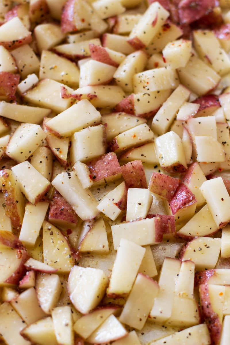 Marinated chopped potatoes in a roasting pan.