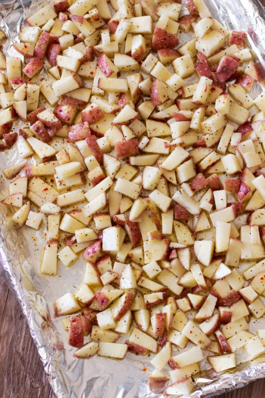 Aluminum foil covered cookie sheet containing marinated red potatoes.