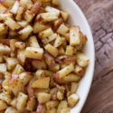 White bowl containing roasted potatoes.