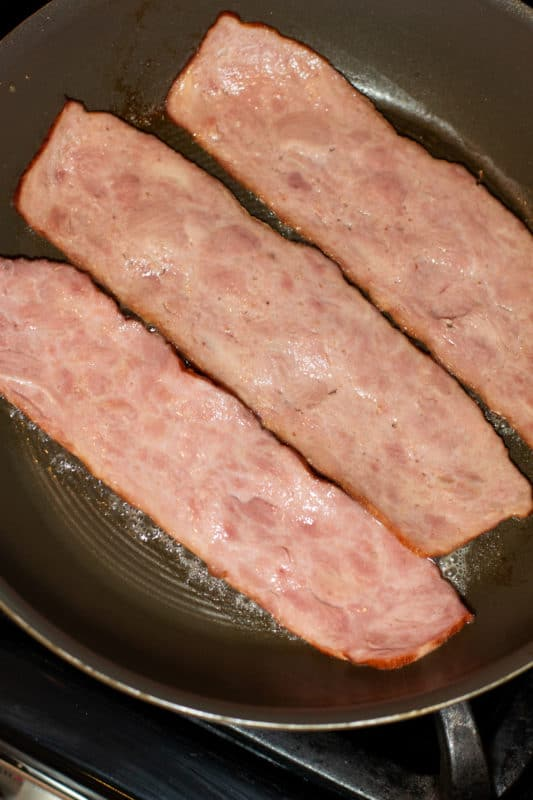 Pan frying bacon in a skillet.