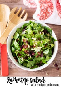 White bowl containing romaine lettuce topped with Havarti cheese and dried cranberries, sunflower seeds and salad tongs on table.