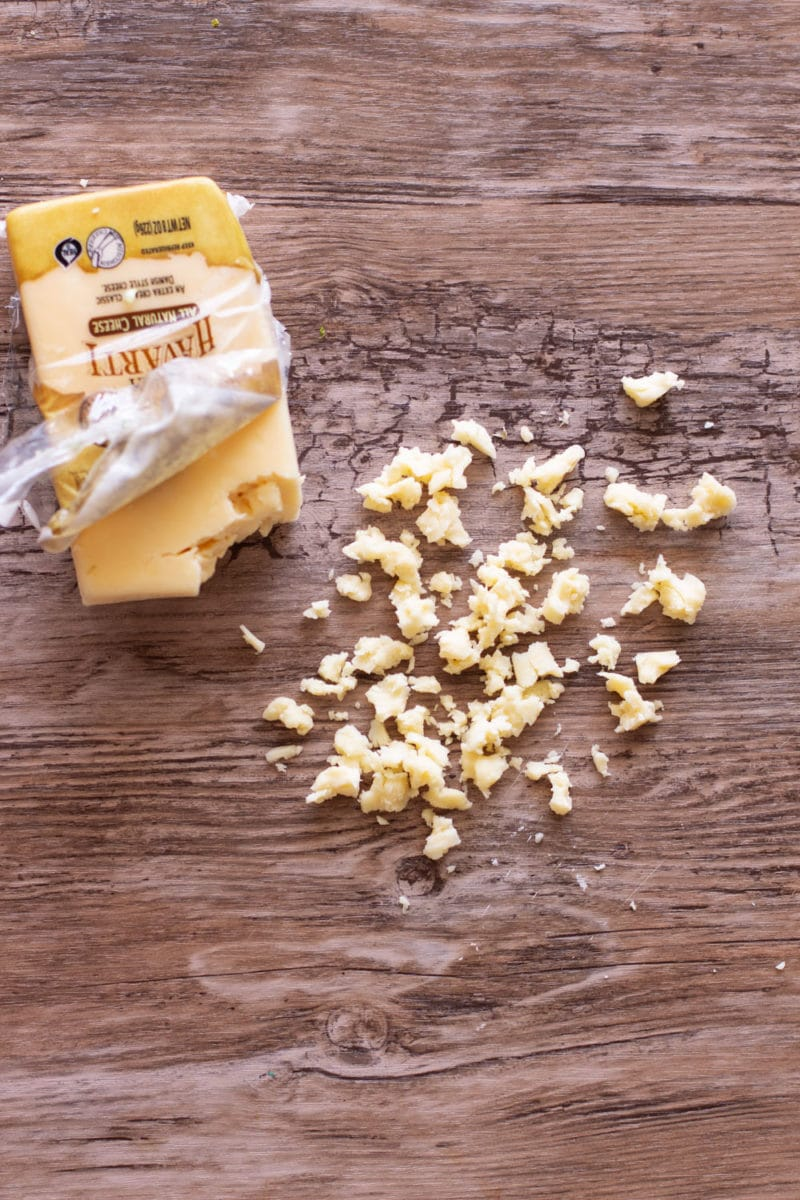 Crumbled Havarti cheese on a wooden table.