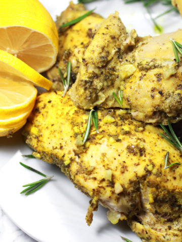 A close up of roasted chicken with fresh herbs and sliced lemons.