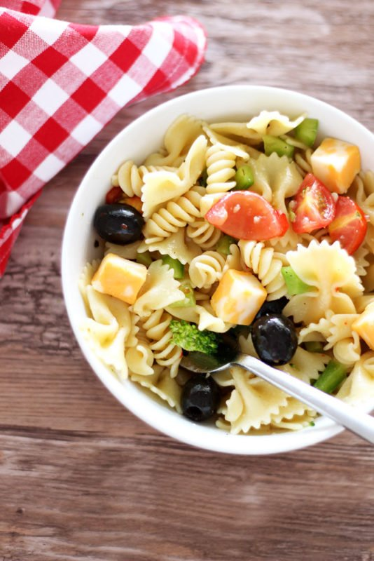 White bowl containing pasta salad topped with tomatoes, peppers, cheese and broccoli, fork in bowl with red gingham napkin on brown table.