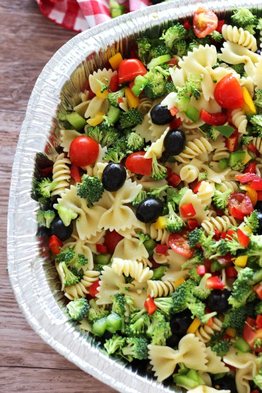 Silver pan containing pasta, broccoli, sweet peppers, tomatoes and black olives sitting on a brown table.
