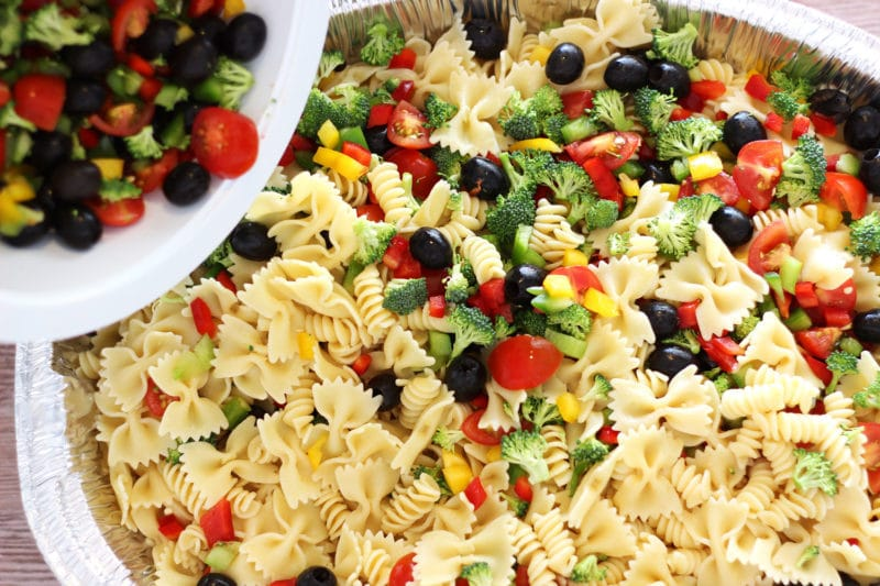 Silver pan containing Italian Style pasta salad with tomatoes, peppers, cheese and broccoli being poured in from a white bowl.