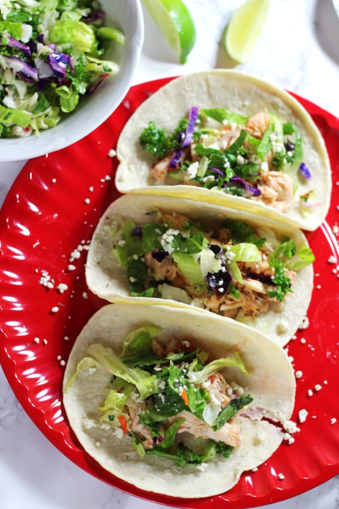 A red plate featuring 2 chicken tacos topped with slaw, lime wedges on a white table.