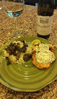 A plate with salmon covered in dill pepperoncini cream sauce with mushroom rice on a counter.